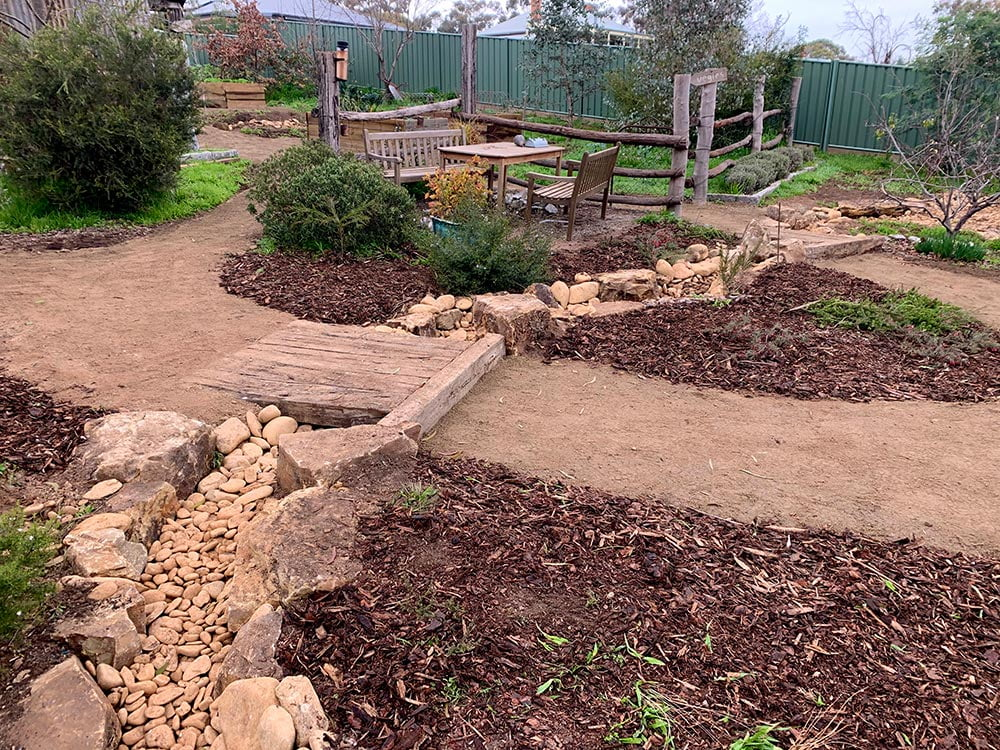 Dry creek bed with sleeper bridge and crushed granite